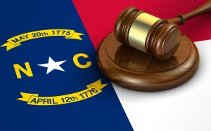 North Carolina US state law code legal system and justice concept with a 3d render of a gavel on the North Carolinian flag on background.